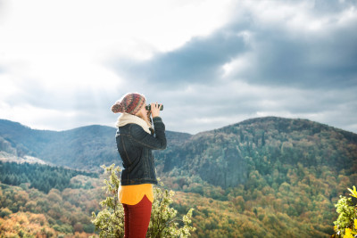 Beautiful woman looking through binoculars against colorful autumn forest, rear view